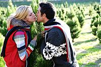 Young couple kissing at Christmas tree lot.