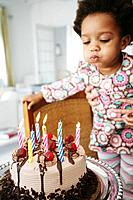 African American child blowing out birthday candles