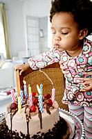 African American child blowing out birthday candles.