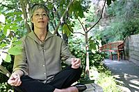 Asian woman doing yoga in garden.