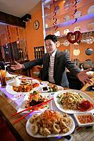 Asian man sitting in restaurant looking at array of food.