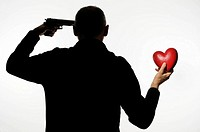Silhouette of man holding heart_shaped object and putting handgun to head
