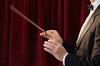 Conductor in front of red curtain, mid section