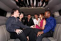 Group of people sitting in limousine, laughing
