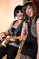 Two young women, one using microphone, other using guitar