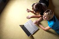 Two young women lying on floor, using laptop, overhead view