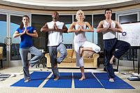 Four people practicing yoga, standing on one leg