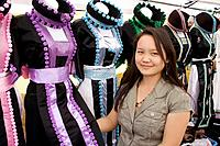 Hmong clerk showing her line of traditional costume dresses  Hmong Sports Festival McMurray Field St Paul Minnesota USA