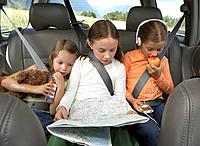 Three girls 6_8 years sitting on rear seat of car on road trip
