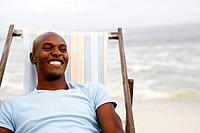 Man relaxing in deckchair on beach, smiling, close_up