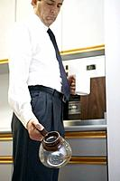 Mature businessman holding empty coffee pot in office kitchen