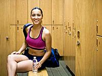 Woman sitting on bench in locker room, portrait