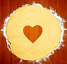 Cookie dough with heart shape cut out, overhead view