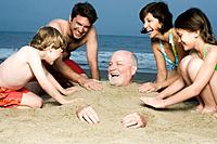 Couple with two children 8_9 burying grandfather in sand on beech