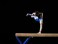 Gymnast 9_10 balancing on balance beam, side view