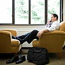 Business man using mobile phone, sitting in armchair