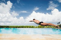 Man diving into swimming pool, mid air, rear view