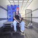 Warehouse worker sitting inside trailer, portrait