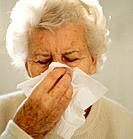 Elderly woman blowing her nose.