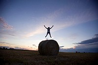 Silhouette of person jumping over large hay bale