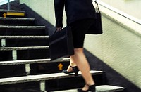 Businesswoman climbing stairs at Tokyo Station, blurred motion. Japan.
