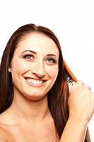 Young woman brushing hair, smiling, studio shot