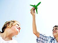 Boy and girl looking up at toy plane (thumbnail)