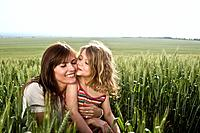 Child kissing mother in wheat_field