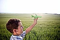 Boy playing with toy plane (thumbnail)