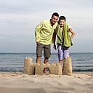 Father and son posing with sandcastle