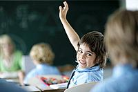 School boy raising hand in class
