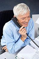 Mature businessman at desk, on phone