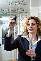 Businesswoman writing keywords on glass