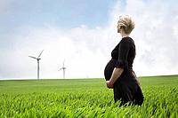 Pregnant woman looking at wind turbines