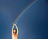 Shirtless man with arms raised and rainbow behind