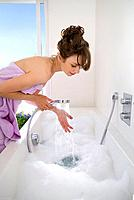 Woman filling bathtub