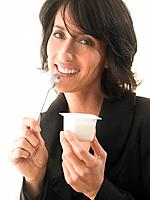 Woman eating yoghurt, smiling