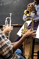 Multi_ethnic students holding trumpets in classroom