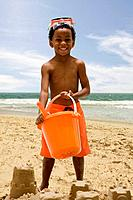 African boy building sand castle on beach
