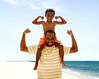 African father and son flexing biceps on beach
