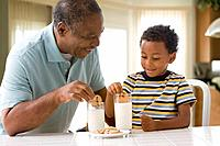 African grandfather and grandson dipping cookies in milk