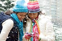 Multi_ethnic girls in snow holding digital camera