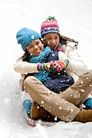 Multi_ethnic girls sledding in snow