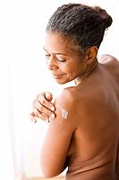 Mixed race woman with bare chest applying lotion to arm