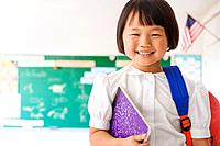Asian girl holding backpack and notebook in classroom