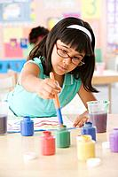 Hispanic school girl painting in classroom
