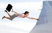 Mixed race businesswoman holding onto airplane wing