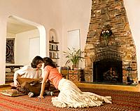 Multi_ethnic couple playing sitar in living room