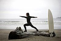 Surfer stretching on beach, Cox Bay near Tofino, British Columbia, Canada