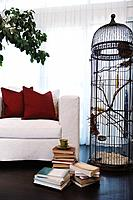 Eclectic living room with stacks of books and large birdcage